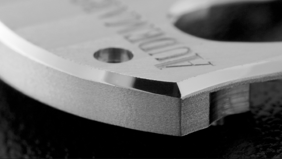 An outward angle on an Audemars Piguet bridge. Before the chamfering process, the flanks of the bridge are drawn: scratches and burrs are removed. Their surface is smoothed down using files, abrasive, grinding wheels guided along the component to form soft straight parallel lines.